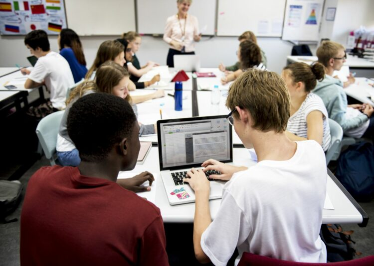 Middle school students do teamwork in a classroom while guided by their teacher.